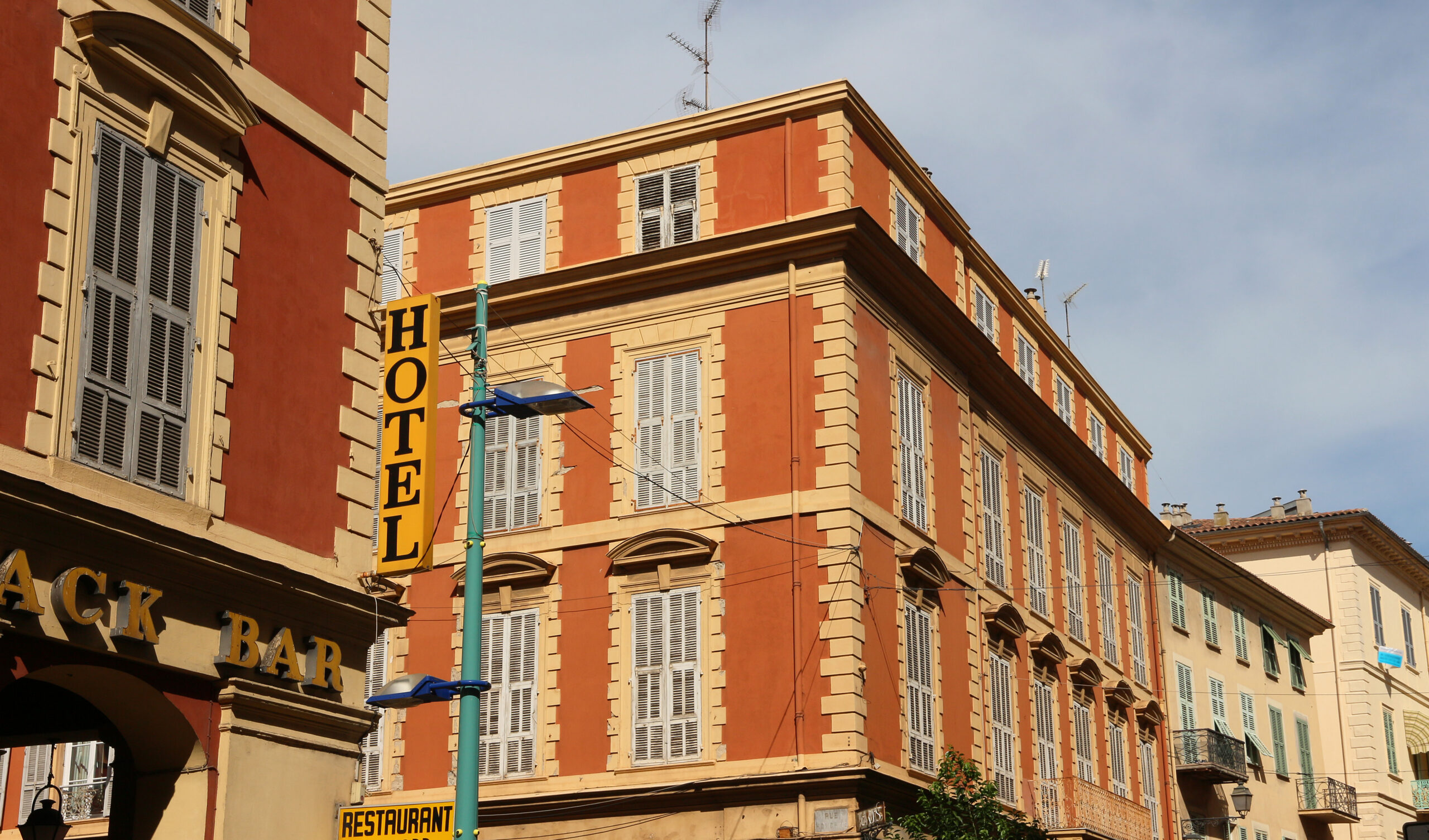 old red buildings in Menton + hotel sign, French Riviera